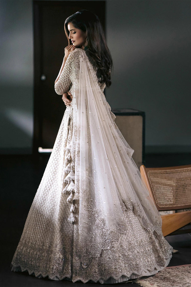 Ivory lehenga with all-over cutdana work in jaal pattern & cutwork hem. Comes with sheer panel blouse & embellished dupatta.