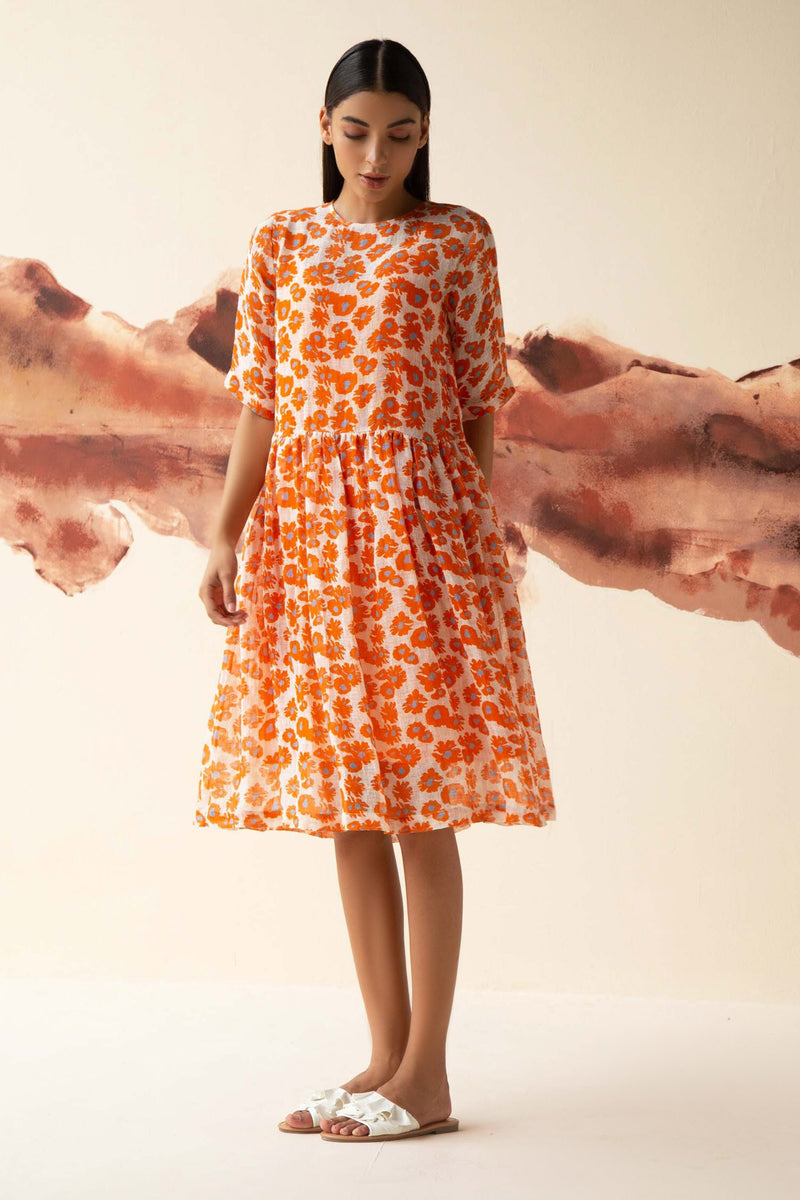 Orange sheer dress with all-over floral print, bottom frill and half sleeves. Comes with a slip.