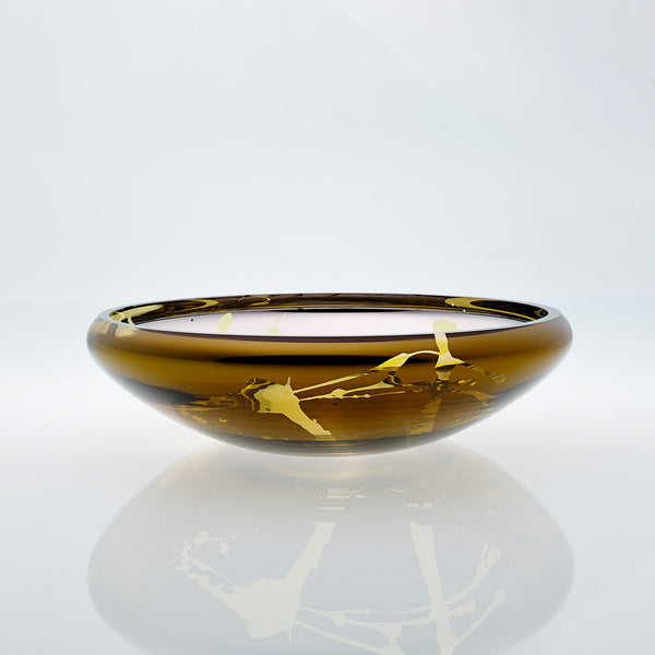 Flat round amber glass bowl with metal interior coating and splashes. Designer glass fruit bowl with mirror effect.