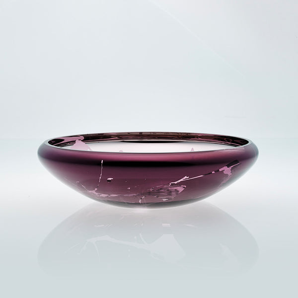 Flat round purple glass bowl with metal interior coating and splashes. Designer glass fruit bowl with mirror effect.