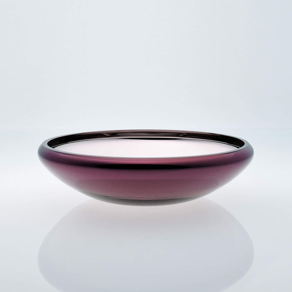 Flat round purple glass bowl with metal interior coating. Designer glass fruit bowl with mirror effect.
