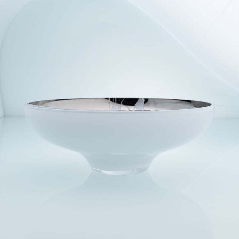 Round white glass fruit bowl on a stand with interior stainless steel coating and splashes. Mirror effect design glass bowl.