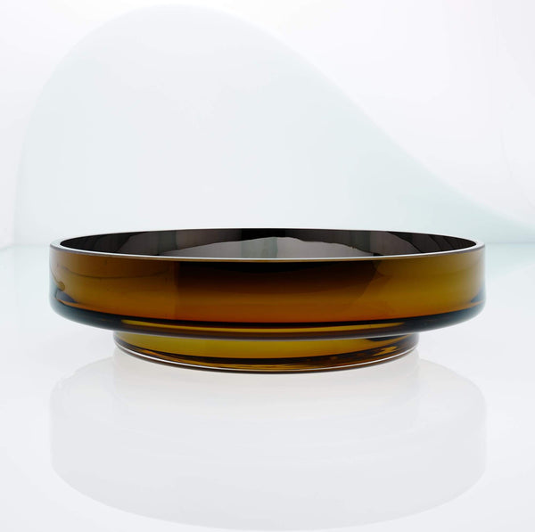 Large, flat disk glass fruit bowl in amber with metal interior coating. Designer hand made glass bowl.