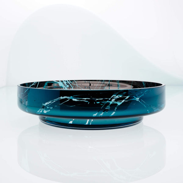 Large, flat disk glass fruit bowl in teal blue with metal interior coating and splashes. Designer hand made glass bowl.