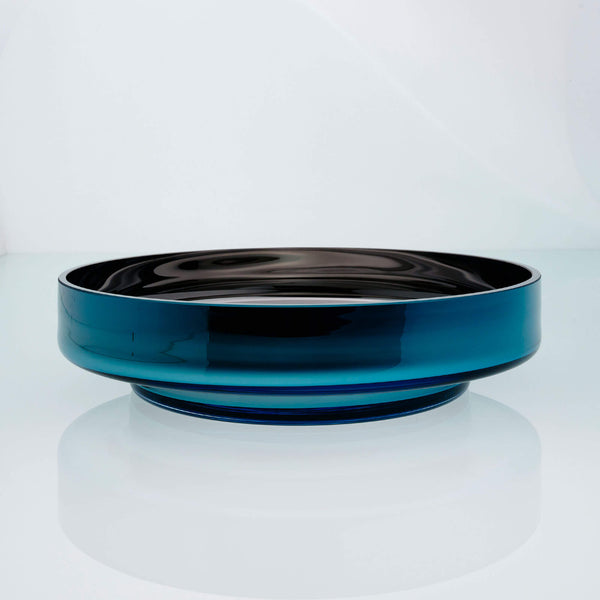 Large, flat disk glass fruit bowl in teal blue with metal interior coating. Designer hand made glass bowl.