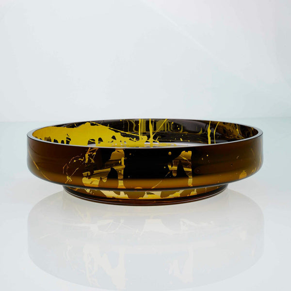 Large, flat disk glass fruit bowl in amber with metal interior coating and splashes. Designer hand made glass bowl.