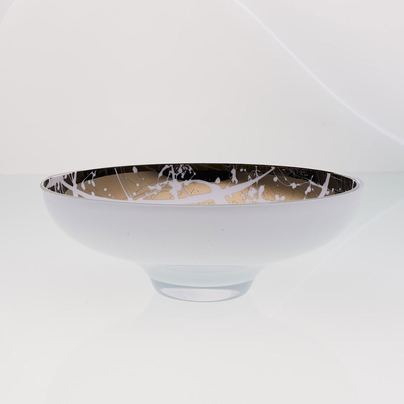 Round white glass fruit bowl on a stand with interior titanium coating and splashes. Mirror effect design glass bowl.