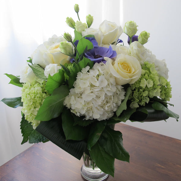 Flowers used: white roses, green and white hydrangeas, green chrysanthemums, purple ranunculus, white lisianthus
