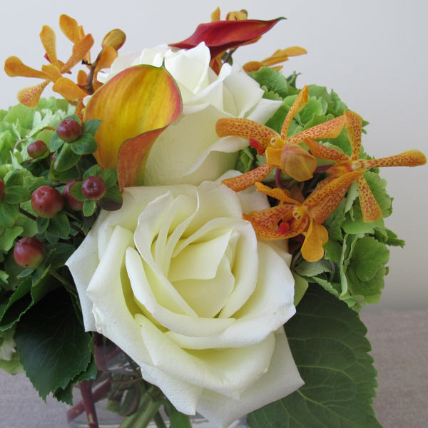 Flowers used: white roses, orange calla lilies, orange mokara orchids, green hydrangeas, hypericum berries