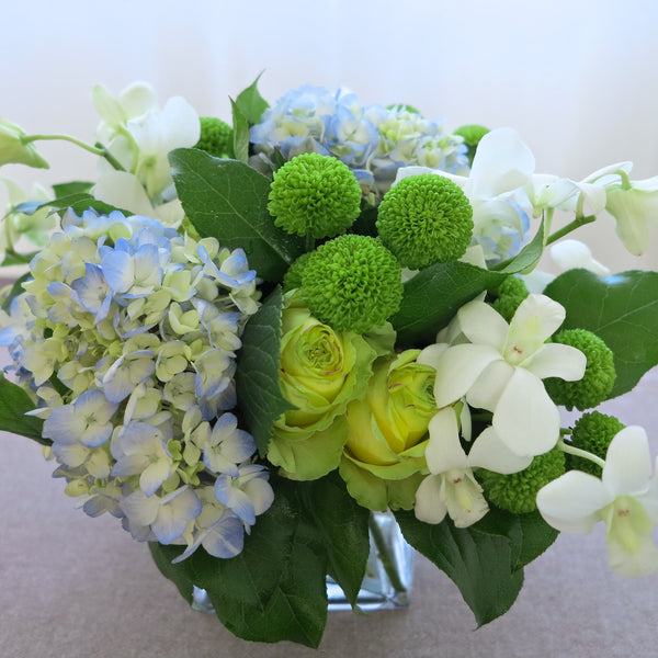 Flowers used: white roses, blue hydrangeas, white orchids, green mini mums