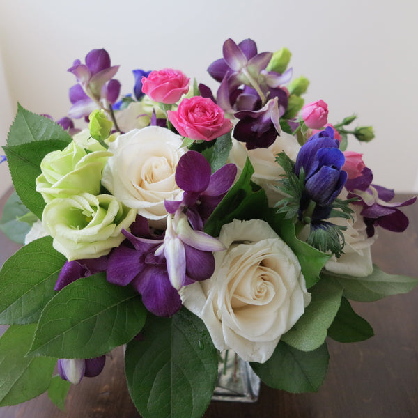 Flowers used: cream white roses, white gerberas, chartreuse lisianthus, blue anemones, pink mini roses, purple orchids