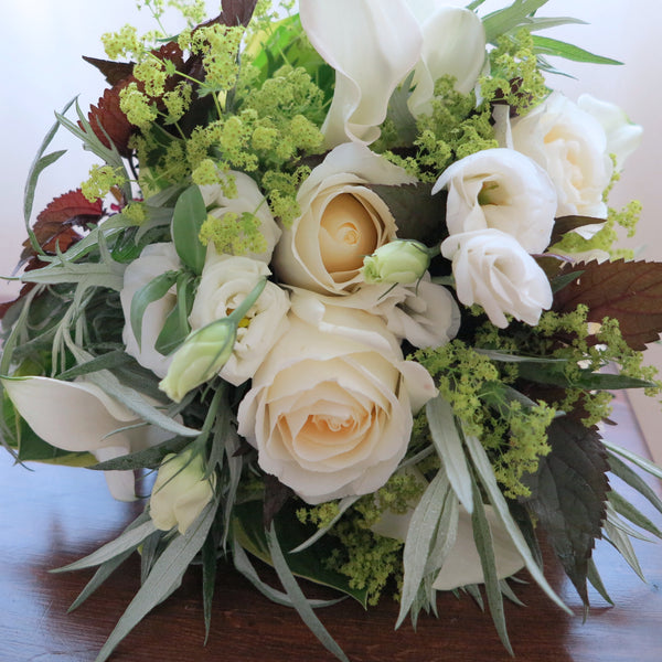 Flowers used: white roses, white calla lilies, white lisianthus, chartreuse lady's mantle
