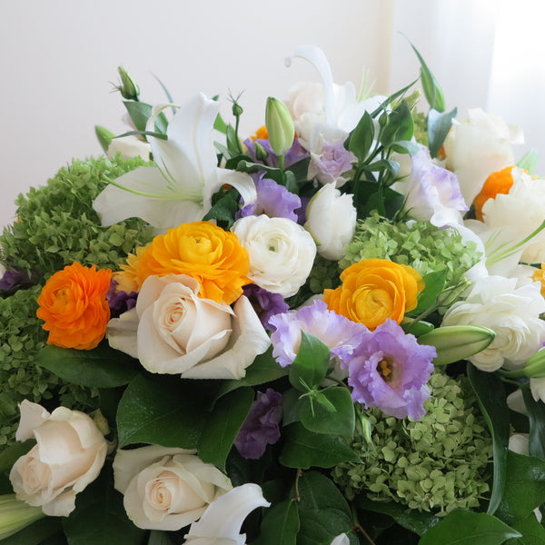 Flowers used: cream roses, white lilies, green hydrangeas, white ranunculus  and purple lisianthus