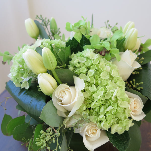 Flowers used: white tulips, cream roses, green viburnums, chartreuse orchids, seeded eucalyptus