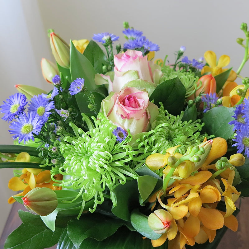Flowers used: blush pink roses, orange orchids, red tulips, green chrysanthemums, blue aster daisies
