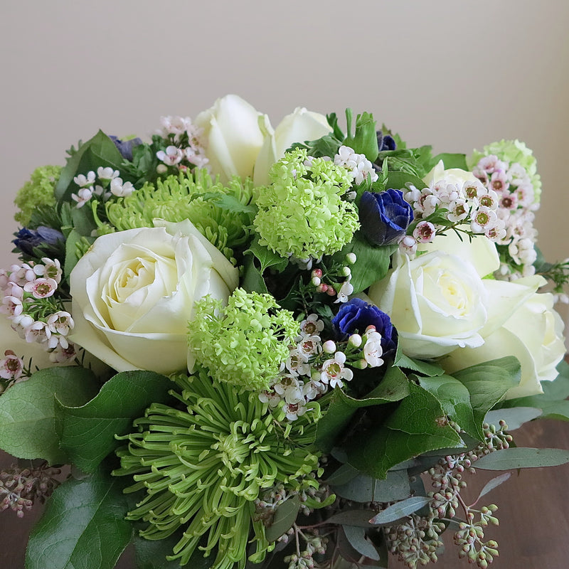 Flowers used: white roses, green chrysanthemums and viburnums blue/purple anemones, wax flowers, seeded eucalyptus