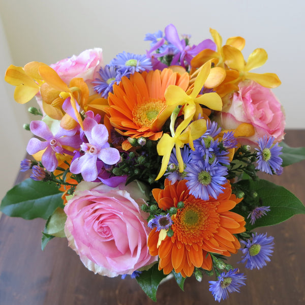 Flowers used: blush pink roses, orange gerberas, yellow, orange and mauve orchids, blue aster daisies