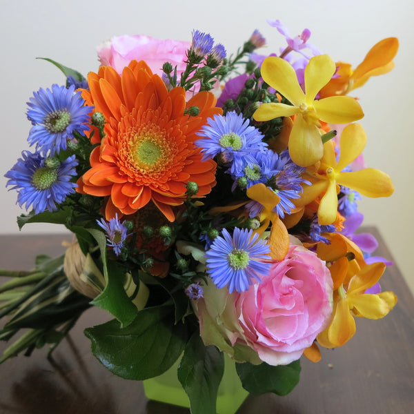 Flowers used: blush pink roses, yellow, orange and mauve orchids, orange gerberas, blue daisies