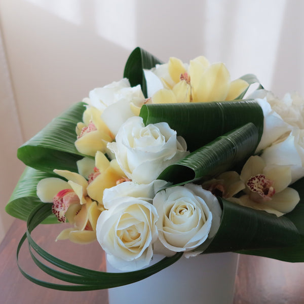 Flowers used: cream white roses, yellow cymbidium orchids