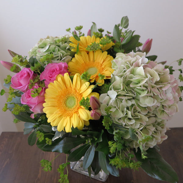 Flowers used: pink roses, yellow gerberas, pink tulips, rustic green hydrangeas, chartreuse lady's mantle