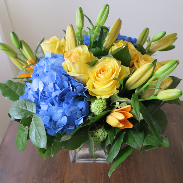 Flowers used: yellow roses, blue hydrangeas, yellow lilies and green viburnums