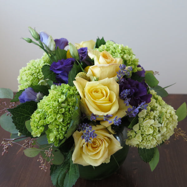 Flowers used: yellow roses, purple lisianthus, green hydrangeas, seeded eucalyptus