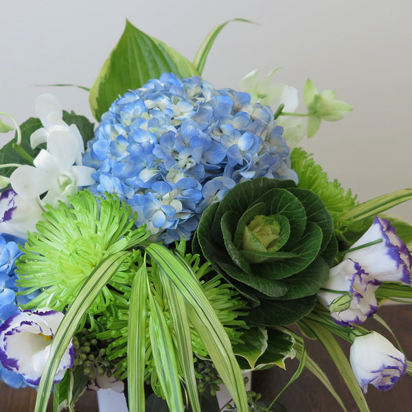 Flowers used: blue hydrangeas, purple/white lisianthus, white orchids, green chrysanthemums, hosta leaves and green kales