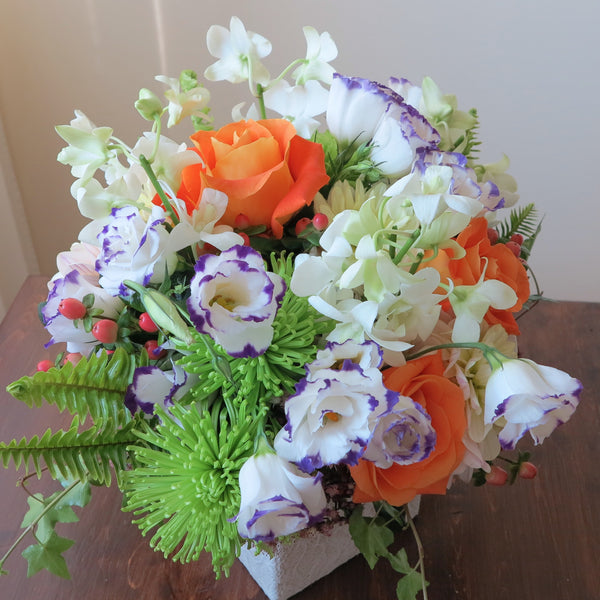 Flowers used: purple/white lisianthus, white orchids, orange roses, green chrysanthemums, pink hypericums and cream dahlias