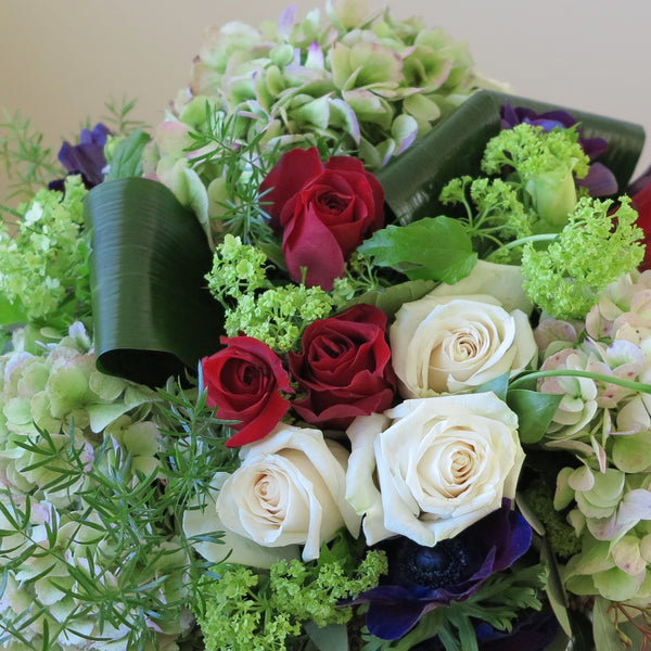 white and burgundy roses, green hydrangeas, purple anemone, blue lisianthus