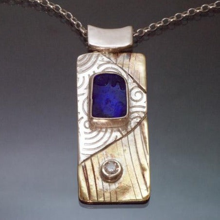long rectangular silver brass necklace with blue beach glass and cubic zirconia, spirals embossed into the silver.