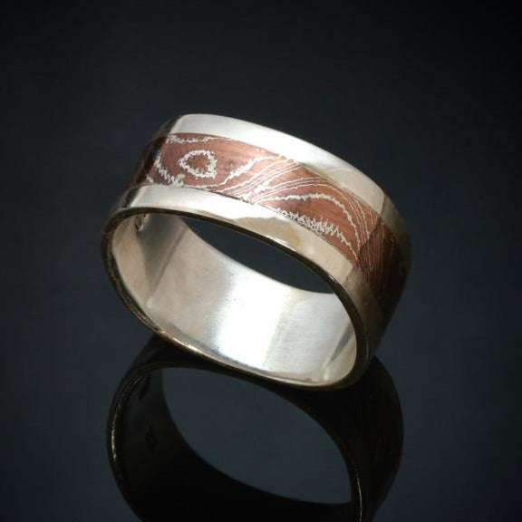 9mm wide Silver band with a centre band of mokume gane. The mokume has a wood grain pattern and is made with copper and silver.