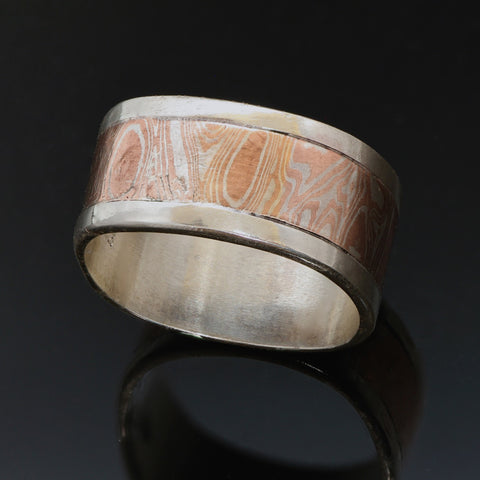11mm wide Silver band with a centre band of mokume gane. The mokume has a wavy wood grain pattern and is made with copper and silver.