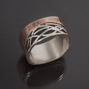 Sterling silver band made with an band of mokume gane contouring waves of sterling silver with recessed parts oxidized black. The mokume is made with copper and silver.