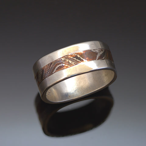 10mm wide Silver band with a centre band of mokume gane. The mokume has a wavy wood grain pattern and is made with copper and silver.