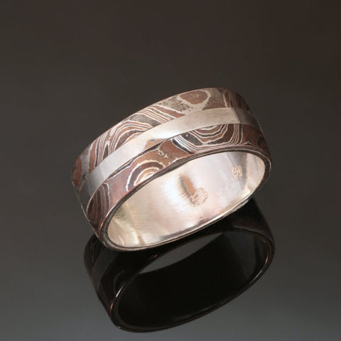 8mm wide Silver band with a centre stripe of Sterling silver and a band of mokume gane on either side of the silver. The mokume is made with copper and silver with a wavy wood grain pattern.