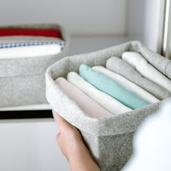 A person carrying a crate of folded and organized towels.