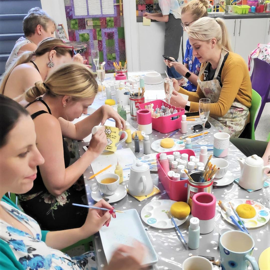 A group of adult pottery painters enjoying a creative evening.