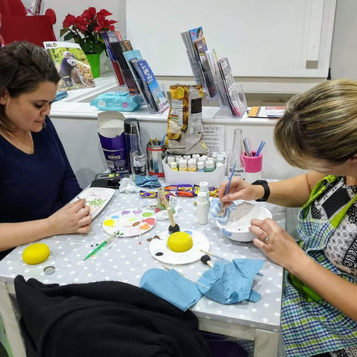 Two of our Evening Session customers putting some finishing touches to their pottery.