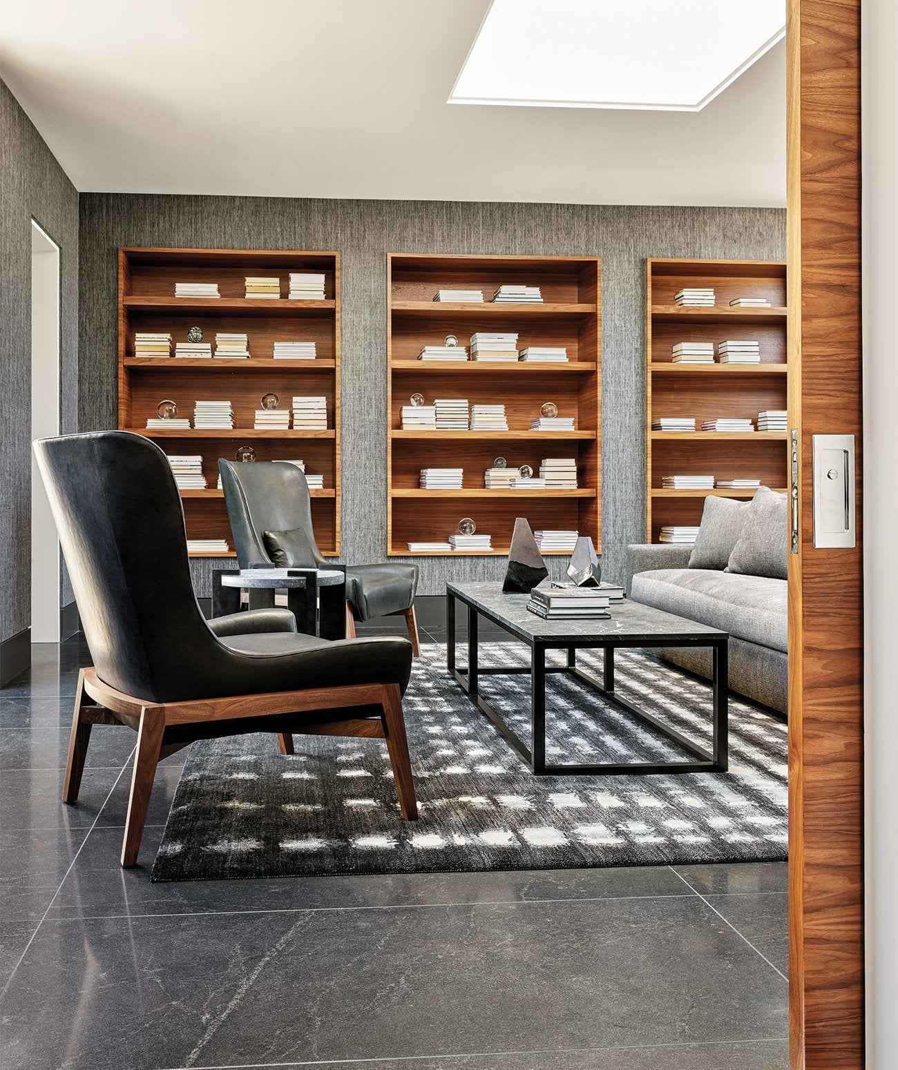 A small neutral, modern library/Photography: Werner Segarra/A textured wallcovering by Phillip Jeffries appears in this modern home library designed by IMI Design Studio.