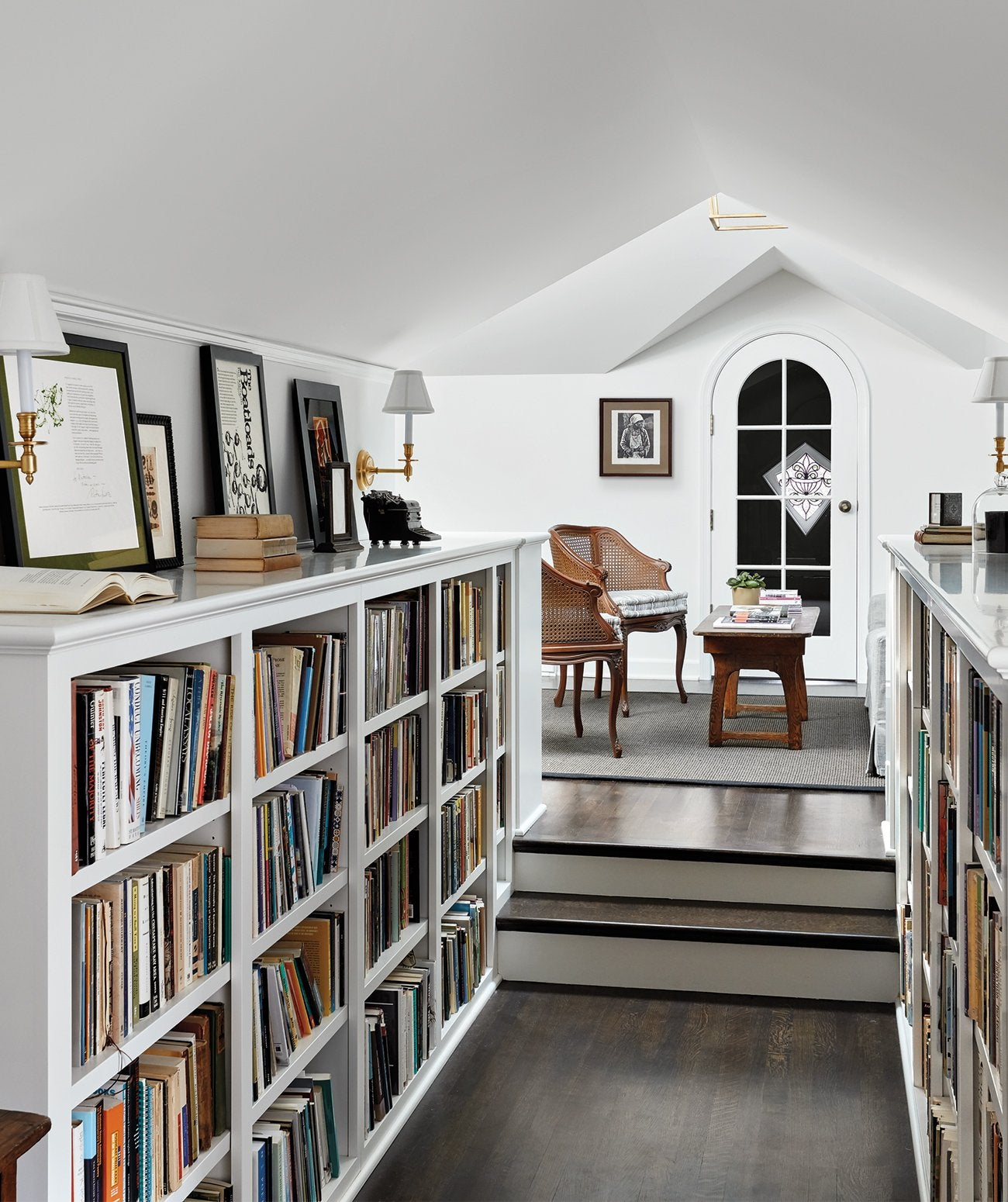 A white home library located in the attic/Photography: Dustin Halleck/An attic-turned-study, this homey room designed by Third Coast Interiors features a restored original window with a fleur-de-lis motif.