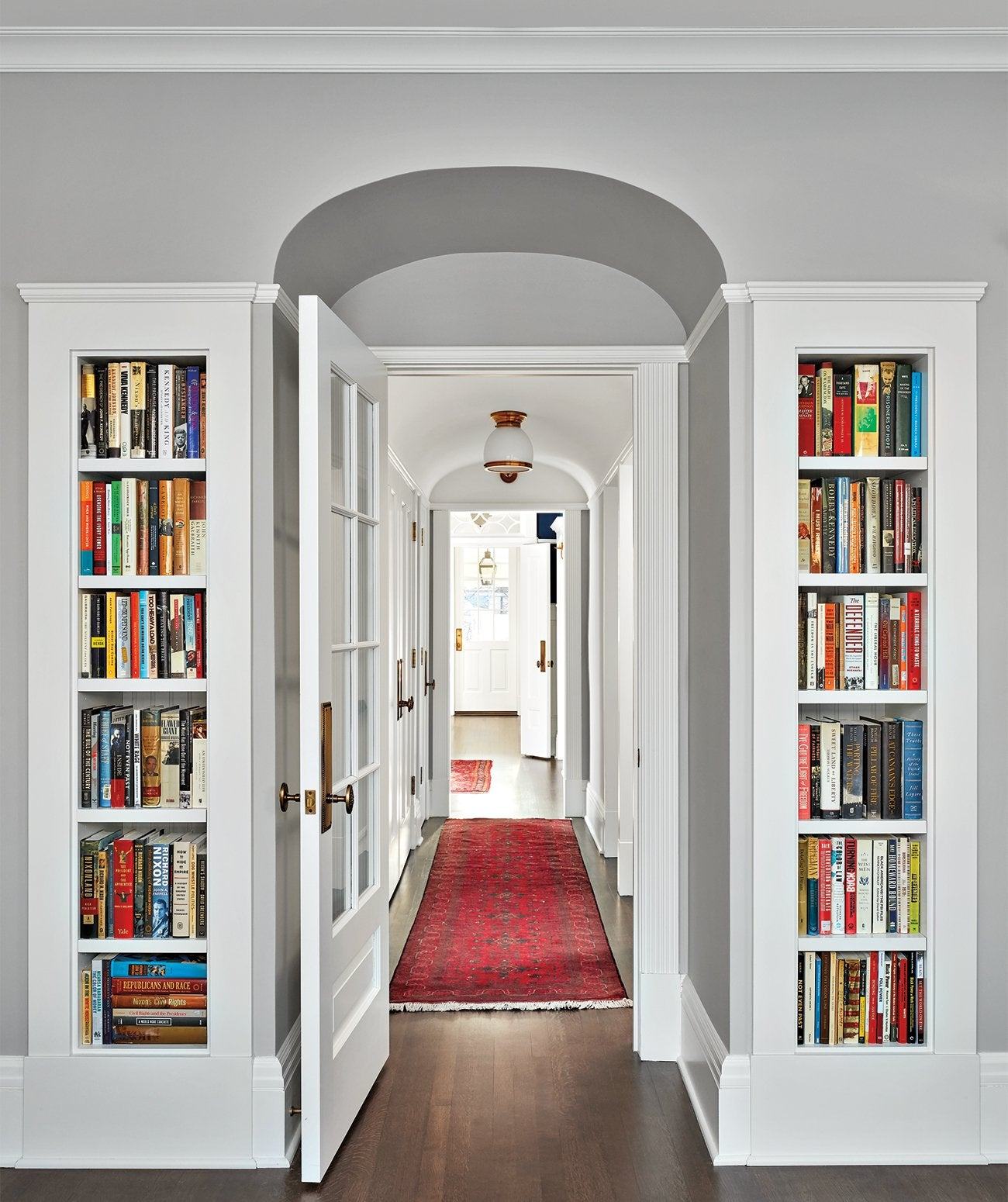 A door frame with bookshelves on either side/Photography:Dustin Halleck/A second book-filled room in the home above, this office features custom bookshelves, and historically accurate hardware and French doors.