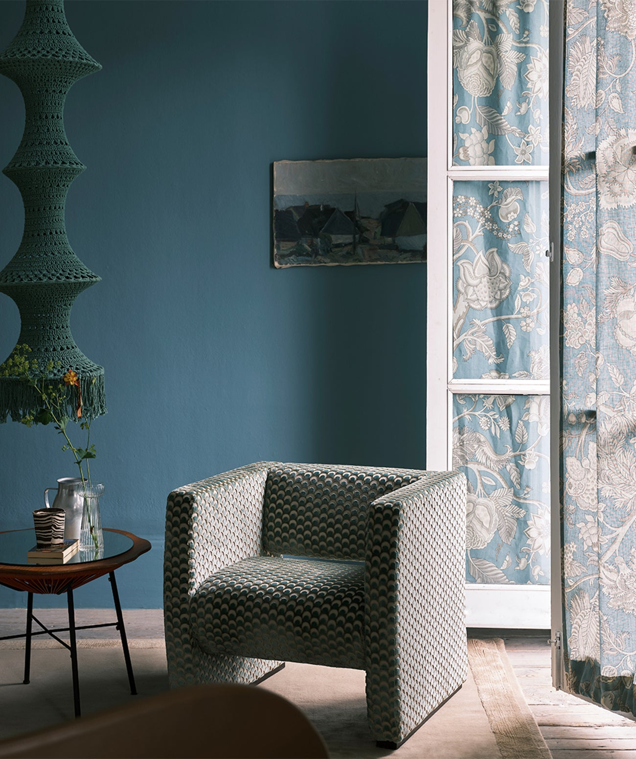A deep blue room featuring upholstered chair and open French door/Photography: Farrow & Ball/Farrow & Ball's Berrington Blue wallcolor complements Liberty's Palampore Trail fabric, of the drapes, and Ottoman Spot, on the upholstered chair.
