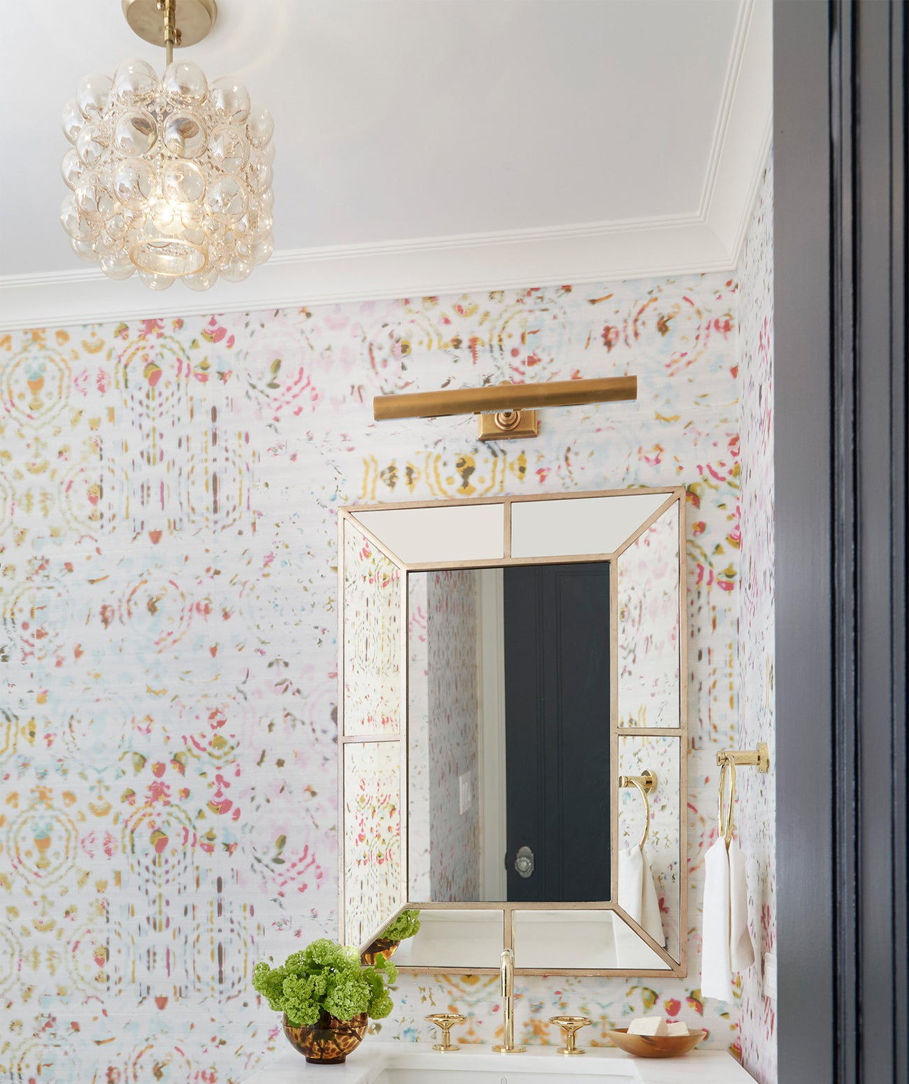 A bright powder room featuring chandelier and patterned wallpaper/Photography: Amy Kartheiser Design/Another powder room means another means chance to play with pattern.