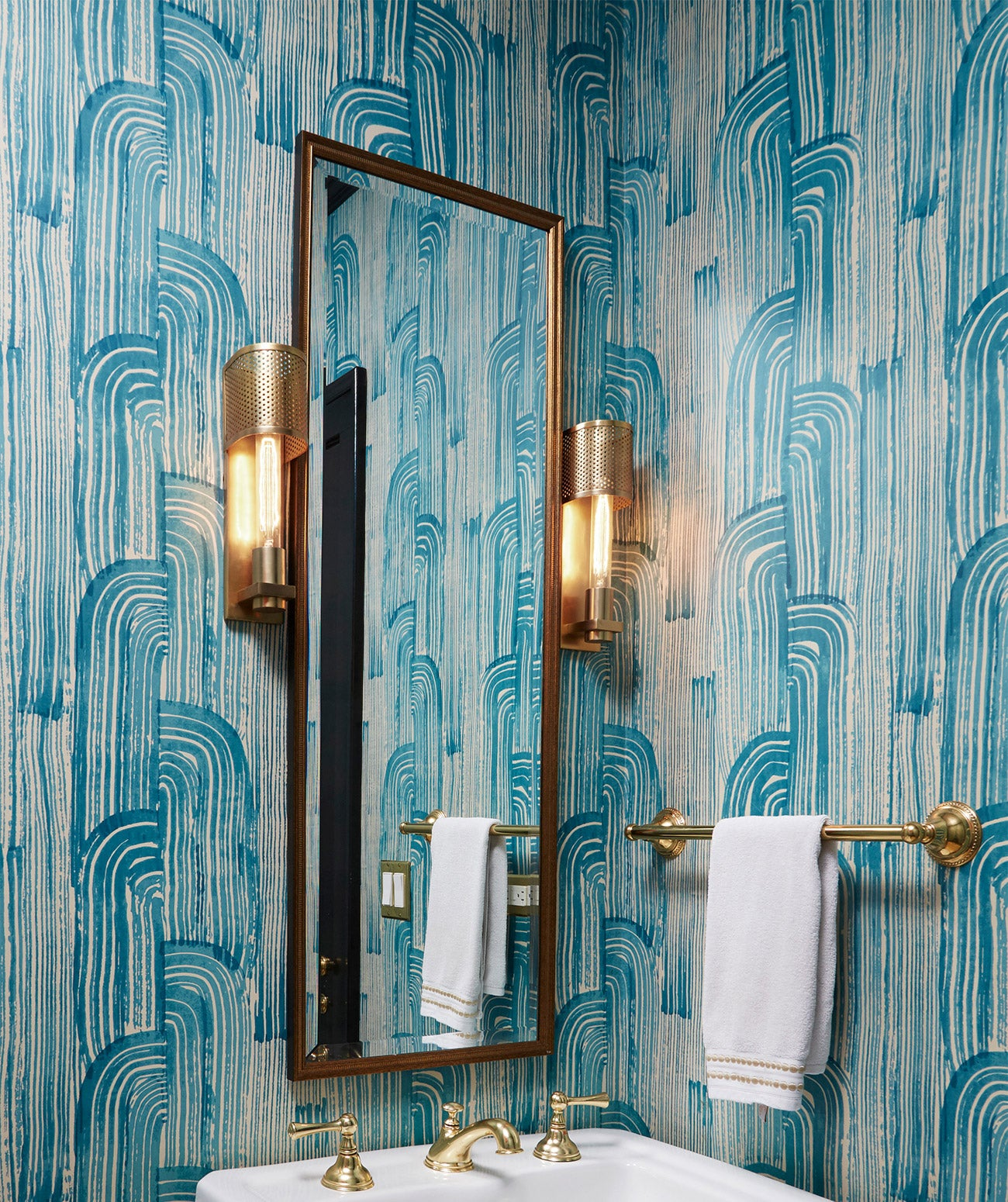 A powder room with blue and white wallpaper/Photography: Amy Kartheiser Design/A moody, modern powder room features graphic blue wallpaper.
