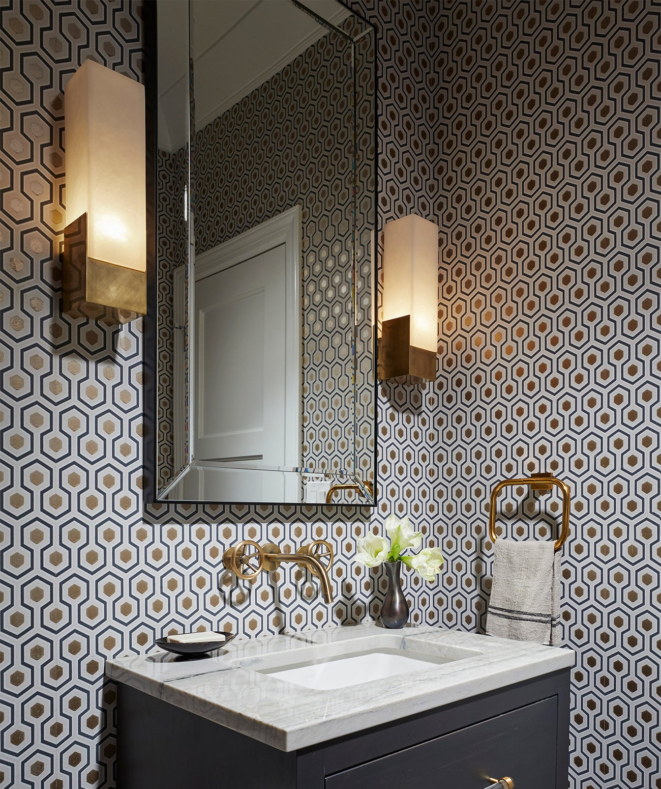 A dark powder room with black and white wallpaper/Photography: Amy Kartheiser Design/A moody powder room features striking geometric wallpaper.