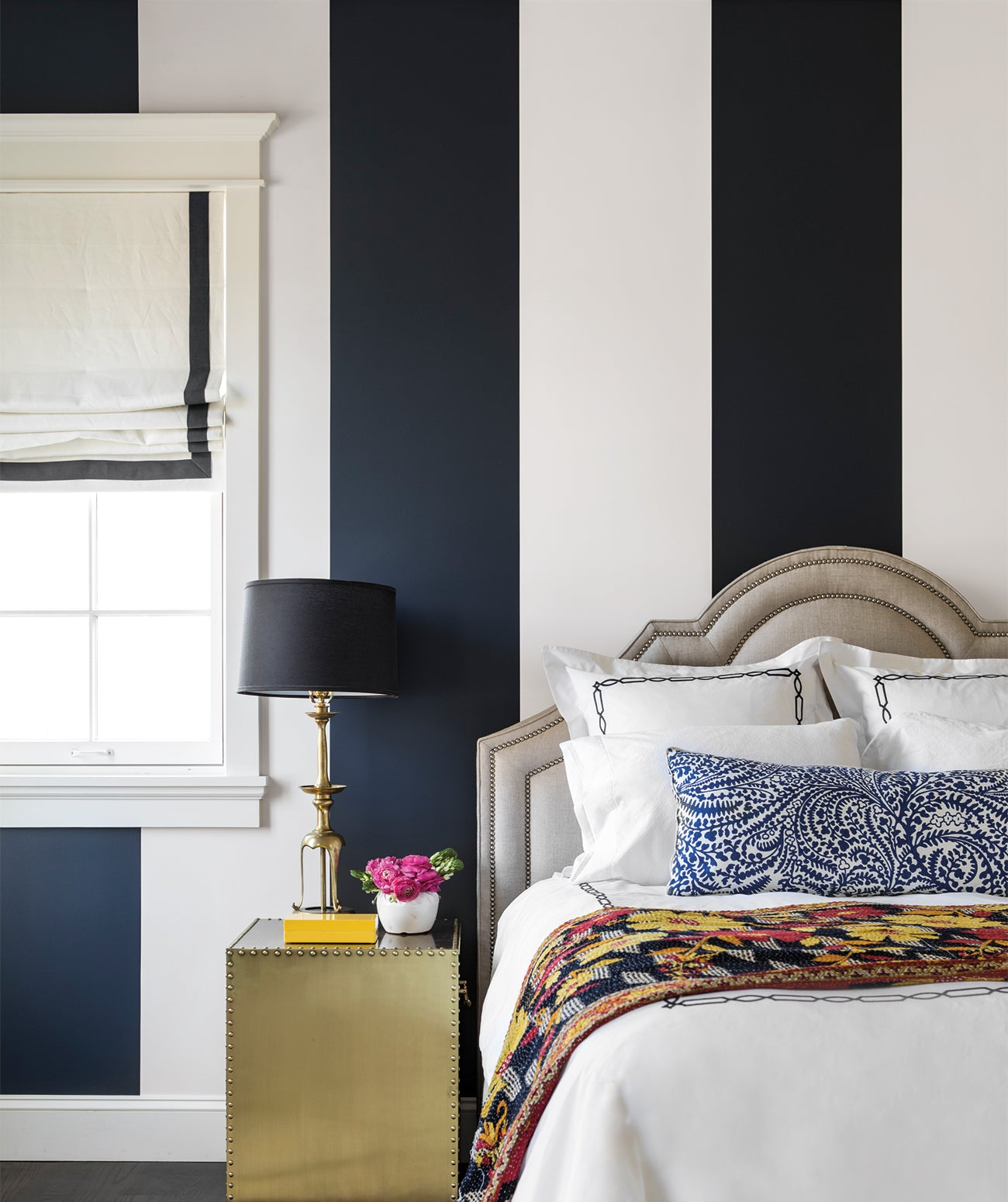 A bedroom with blue and white stripe wall decor/Photography: Laure Joliet/Go classic: These navy and white striped walls make for a tailored, crisp look in this bedroom designed by Barta Interiors.