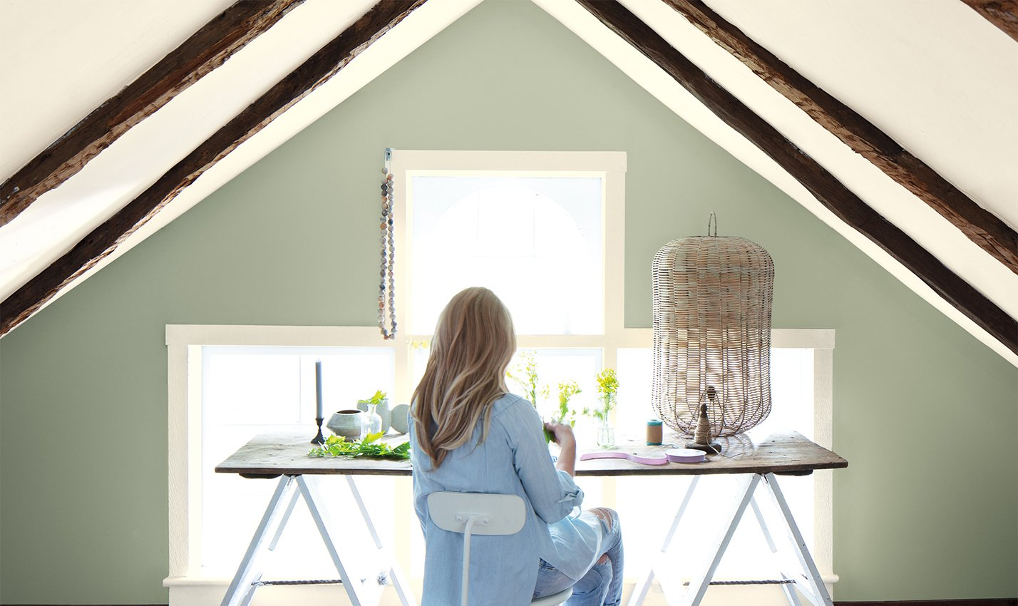 A pale sage wall with sofa and tree/Photography: Benjamin Moore/Benjamin Moore's October Mist 1495, seen here, joins 14 other colors in the brand's 2022 palette.
