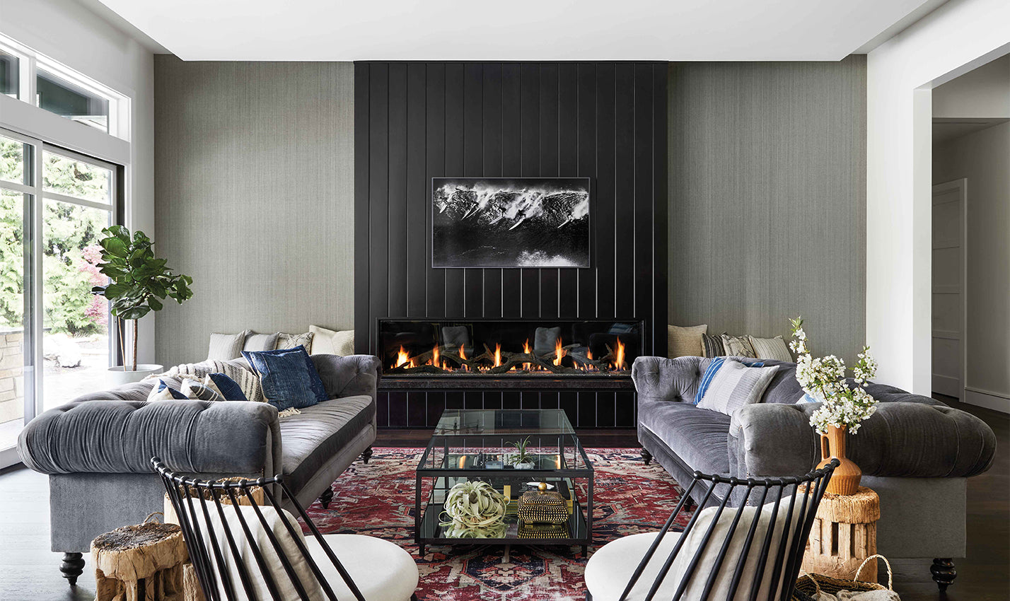A modern living room with fireplace/Photography: Cody Ulrich/This modern great room, designed by Alison Lind for a lake home in Washington state, features a fireplace framed by black-stained fir paneling and granite.