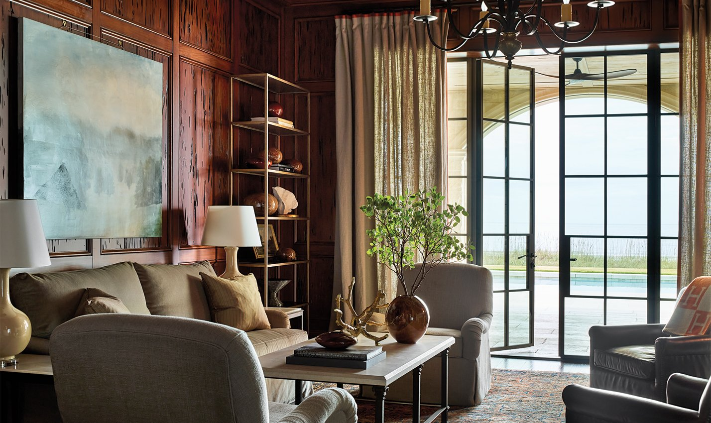 A brown library/Photography: Emily Followill Photography/A moody, masculine study designed by Suzanne Kasler Interiors features stained walls and peaceful views.