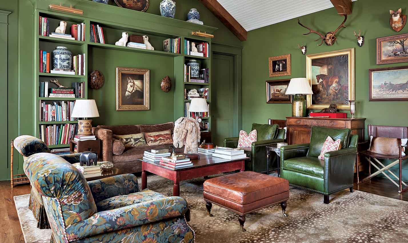 A deep green den/Photography: Dustin Peck/This deeply cozy den, designed by Tom Bossard and Len Cherry and painted in Farrow & Ball's Bancha green, exudes cozy comfort. Shop Farrow & Ball's Bancha green samples to recreate the vibe.